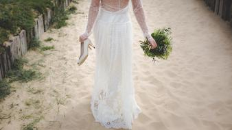 Girl in bridal dress walking barefeet on sand with shoes and bouquet