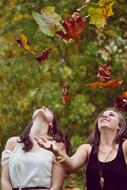two young Girls plays with Autumn Leaves
