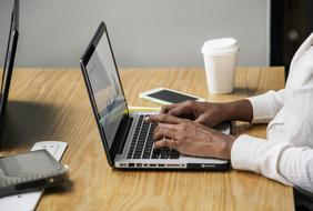 hands of african Businesswoman on keys of laptop