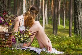 Picnic, young girl sits on forest floor at baskets with flowers