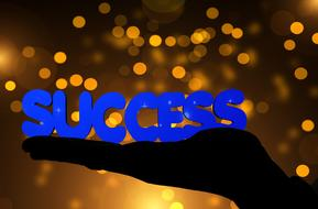 success, blue letters on hand at bokeh background