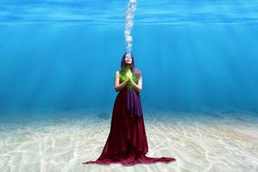woman in long dress stands on seabed underwater, collage
