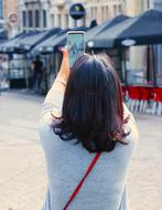 Woman taking photo with Smartphone in city