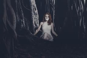 young sexy Woman with cloth on mouth sits in dark Forest, collage