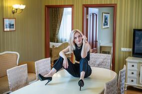 cool Blonde Girl sits on table in living room