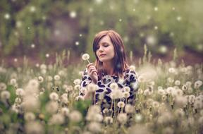 Woman with white dandelion on Meadow