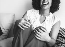 laughing African woman sits on Couch