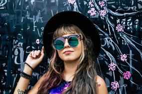 young girl in steampunk glasses posing at painted wall