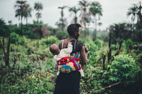 african woman with baby on back in wilderness