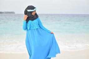 Muslim woman in blue long dress and black Hijab posing at sea
