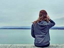 Girl in blue hoodie Looking at sea