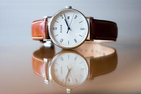 classic Analog Wrist Watch on mirroring surface