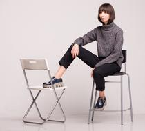 Young woman in stylish shoes sits on black chair with foot on white chair