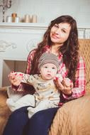 Family love, happy young mother with baby son sitting on armchair