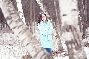 Pretty young Girl among birch trees at winter