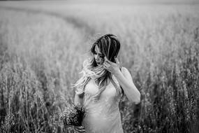 young pregnant woman stands with bouquet in front of field