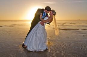 newlyweds kiss on the evening beach