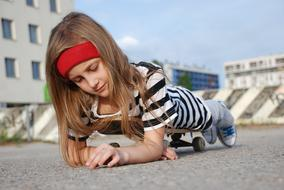 pretty child Girl laying on Skateboard
