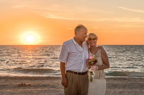 elderly bride and groom on the evening beach