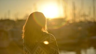 photo of a girl on a background of bright sunrise
