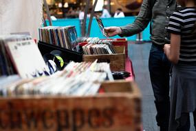 people at market stall with music records