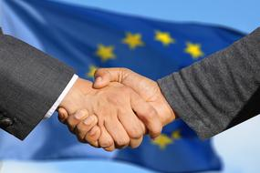 Friendship, handshaking at flag of European union