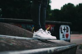 photo of girls legs in white sneakers
