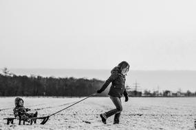 mother pulling sled with Baby in countryside