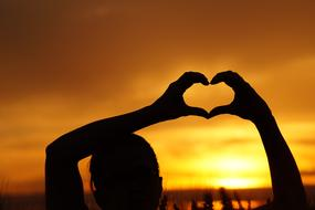 Love, heart gesture at sunset sky