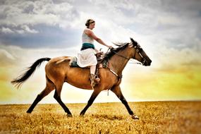 woman Riding Horse on harvested field