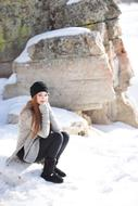 girl is sitting on a stone on the background of a snowy rock