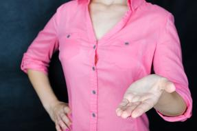 woman in pink shirt holding palm open