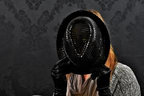 woman hiding her face with black hat