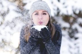 Woman in grey hat blowing on snow on her hands
