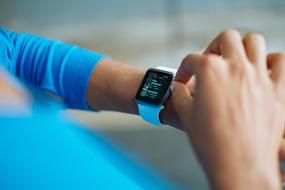photo of a blue smart watch on a girl's hand