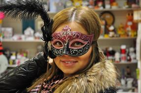 smiling blonde girl with carnival Mask on face in shop