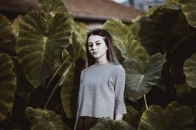photo of a girl on a background of burdock leaves