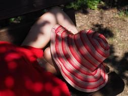 girl is sleeping on a bench with a striped hat on her face