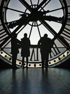 silhouettes of people on the background of a tower clock