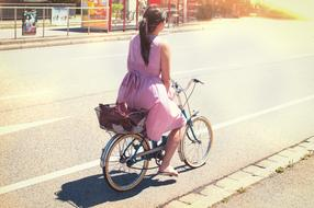 Woman in pink Dress riding bicycle on road