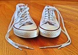 pair of white Converse Sneakers on wooden floor
