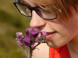 young girl Smelling thistle flowers