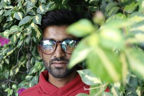 Indian student in glasses on a background of green bush