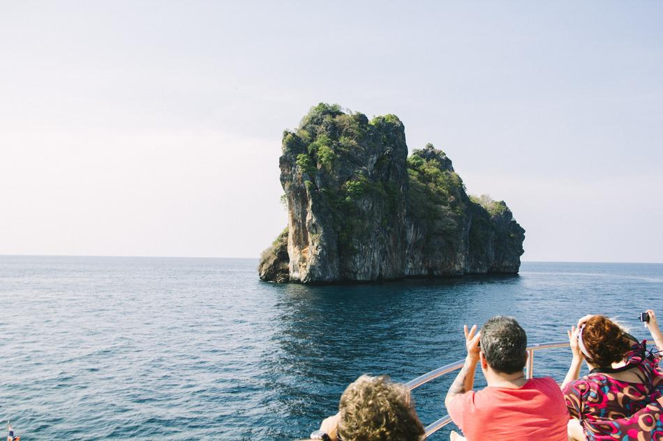 People on boat looking at scenic rock formation in sea