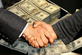 Conclusion Of The Contract, handshaking in front of money suitcase