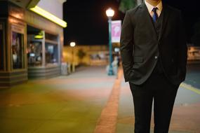 Man in Business suit walking on street at dusk