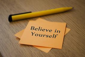 believe in yourself, motivation on yellow sticker and pen