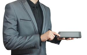 man in grey suit with tablet