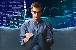 young caucasian man sits in front of screen with trading courses