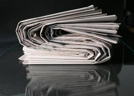 stack of newspapers on a glass table